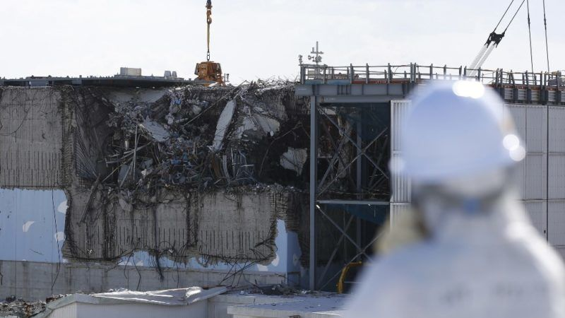 A member of the media, wearing a protective suit and a mask, looks at the No. 3 reactor building during a press tour at Tokyo Electric Power Co's (TEPCO) tsunami-crippled Fukushima Daiichi nuclear power plant in the town of Okuma, Fukushima prefecture on February 10, 2016.  The media tour of the facilities came as Japan readied to mark the fifth anniversary of the March 11, 2011 earthquake and tsunami that caused disastrous meltdowns at the Fukushima nuclear power plant.     AFP PHOTO / POOL / Toru HANAI (Photo by TORU HANAI / POOL / AFP)