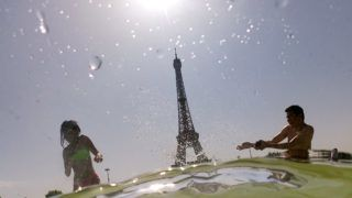 People cool off at the Trocadero Fountains next to the Eiffel Tower in Paris, on July 25, 2019 as a new heatwave hits Europe. - After all-time temperature records were smashed in Belgium, Germany and the Netherlands on July 24, Britain and the French capital Paris could on July 25 to see their highest ever temperatures. (Photo by Dominique FAGET / AFP)