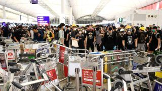 """Pro-democracy protestors block the entrance to the airport terminals after a scuffle with police at Hong Kong's international airport late on August 13, 2019. - Chaos erupted at Hong Kong's airport for a second day on August 13, 2019 as pro-democracy protesters staged a disruptive sit-in that paralysed hundreds of flights, defying warnings from the city's leader who said they were heading down a """"path of no return"""".The latest protest witnessed especially ugly scenes at one of the world's busiest airports as small groups of hardcore demonstrators turned on two men they accused of being spies or undercover police -- and as desperate travellers pleaded in vain to be allowed onto flights. (Photo by Manan VATSYAYANA / AFP)"""