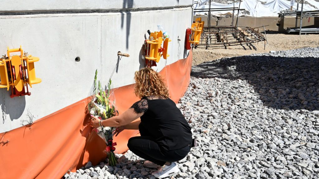A woman deposits a flower bouquet in front of the new bridge pylon afther the mass for the first anniversary of the Morandi's bridge fall, in Genoa, on August 14, 2019. (Photo by Alberto PIZZOLI / AFP)