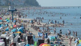 23 July 2019, Mecklenburg-Western Pomerania, Heringsdorf: Hundreds of tourists are looking for cooling off at the Baltic Sea on the island of Usedom. During the prevailing heat, the beach is densely populated. Photo: Stefan Sauer/dpa-Zentralbild/dpa