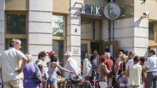Kecskemét, 2014. július 7. Ügyfelek várakoznak az Orgovány és Vidéke Takarékszövetkezet kecskeméti fiókja elõtt 2014. július 7-én, miután a Magyar Nemzeti Bank visszavonta a pénzintézet engedélyét. Korábban a Szövetkezeti Hitelintézetek Integrációs Szervezete (SZHISZ) kizárta az integrációs rendszerbõl a takarékszövetkezetet. MTI Fotó: Ujvári Sándor