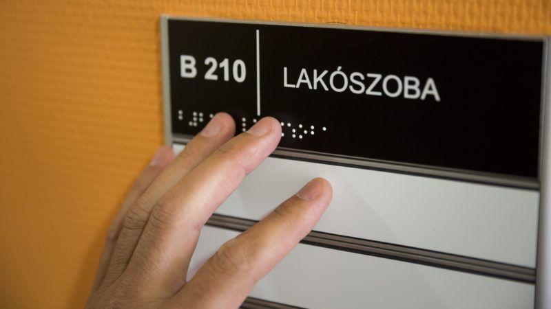 Budapest, 2014. szeptember 19. Egy lakó Braille-írásos táblát olvas a Vakok Állami Intézete Hermina úti felújított épületében 2014. szeptember 19-én. Az intézmény a 600 millió forintos beruházás során új funkciókat is kapott, benne lesz az Országos Módszertani Központ és az Országos Látásvizsgáló és Állapotfelmérõ Központ. MTI Fotó: Mohai Balázs