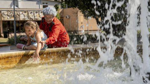 Orosháza, 2019. augusztus 12. Egy nagymama az unokájával hûsöl egy szökõkútnál Orosházán 2019. augusztus 12-én. A kánikula miatt hõségriasztást adott ki az országos tisztifõorvos hétfõ éjfélig. Jelentõs lehûlést hoz a másnap érkezõ hidegfront, 10 fokot, néhol akár többet is csökken a csúcshõmérséklet pár nap alatt. MTI/Rosta Tibor