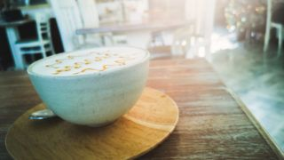 Hot coffee with milk foam and caramel on a wooden table
