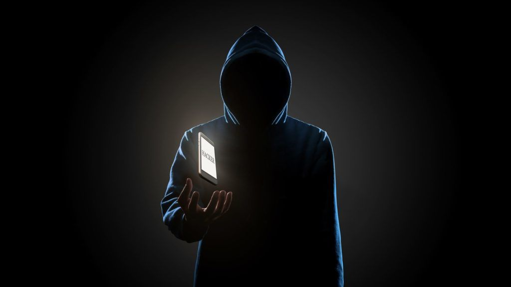 """White smartphone with text """"HACKER"""" on screen floating above of hacker's hand in dark background. Finance, business, e-commerce or cyber crime concept"""