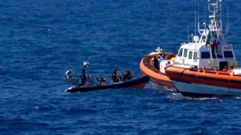 """This grab from a video taken by Local Team shows migrants rescued for days by NGO Proactiva Open Arms charity ship, being rescued by a Spanish patrol boat after throwing themselves in the water to try and swim to the nearby Italian island of Lampedusa in a desperate move after days stuck on board, on August 20, 2019. - The NGO Proactiva Open Arms that owns the ship warned the situation was """"out of control"""" as Spain announced it would make a new attempt at solving a standoff between the vessel and Italy, which refuses them port access. (Photo by - / LOCALTEAM / AFP) / RESTRICTED TO EDITORIAL USE - MANDATORY CREDIT """"AFP PHOTO / LOCAL TEAM""""- NO MARKETING - NO ADVERTISING CAMPAIGNS - DISTRIBUTED AS A SERVICE TO CLIENTS"""