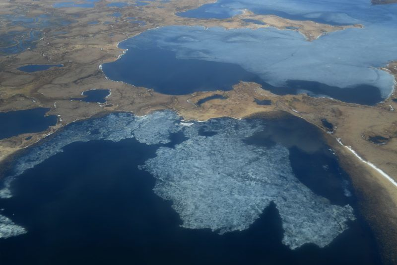 """Aerial view of melting permafrost tundra and lakes near the Yupik Eskimo village of Quinhagak on the Yukon Delta in Alaska on April 12, 2019. - According to scientists, Alaska has been warming twice as fast as the global average, with temperatures in February and March shattering records. """"From 1901 to 2016, average temperatures in the mainland United States increased by 1.8 degrees Fahrenheit (one degree Celsius), whereas in Alaska they increased by 4.7 degrees,"""" said Rick Thoman, a climate expert at the Alaska Center for Climate Assessment and Policy. (Photo by Mark RALSTON / AFP)"""