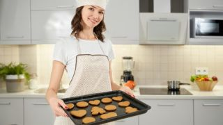Young woman in apron and chef hat holding baking sheet with cookies. Homemade delicious pastry on black baking tray. Beautiful girl with brunette hair in kitchen smiling and looking at camera.