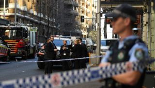 """Police gather at the crime scene after a man stabbed a woman and attempted to stab others in central Sydney on August 13, 2019, before being pinned down by members of the public and detained by police. - Police said the woman was in a stable condition and there were no immediate reports of other injuries, despite """"a number of attempted stabbings by the same offender."""" (Photo by Saeed KHAN / AFP)"""