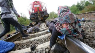 13 August 2019, Lower Saxony, Wolfsburg: Environmental activists chained themselves to a train with new vehicles that had left the VW plant in Wolfsburg during a blockade on a track. Several activists stopped a train in Wolfsburg on Tuesday. A police spokesman said on Tuesday that the car train was loaded with new vehicles to be delivered. Photo: Bodo Marks/dpa