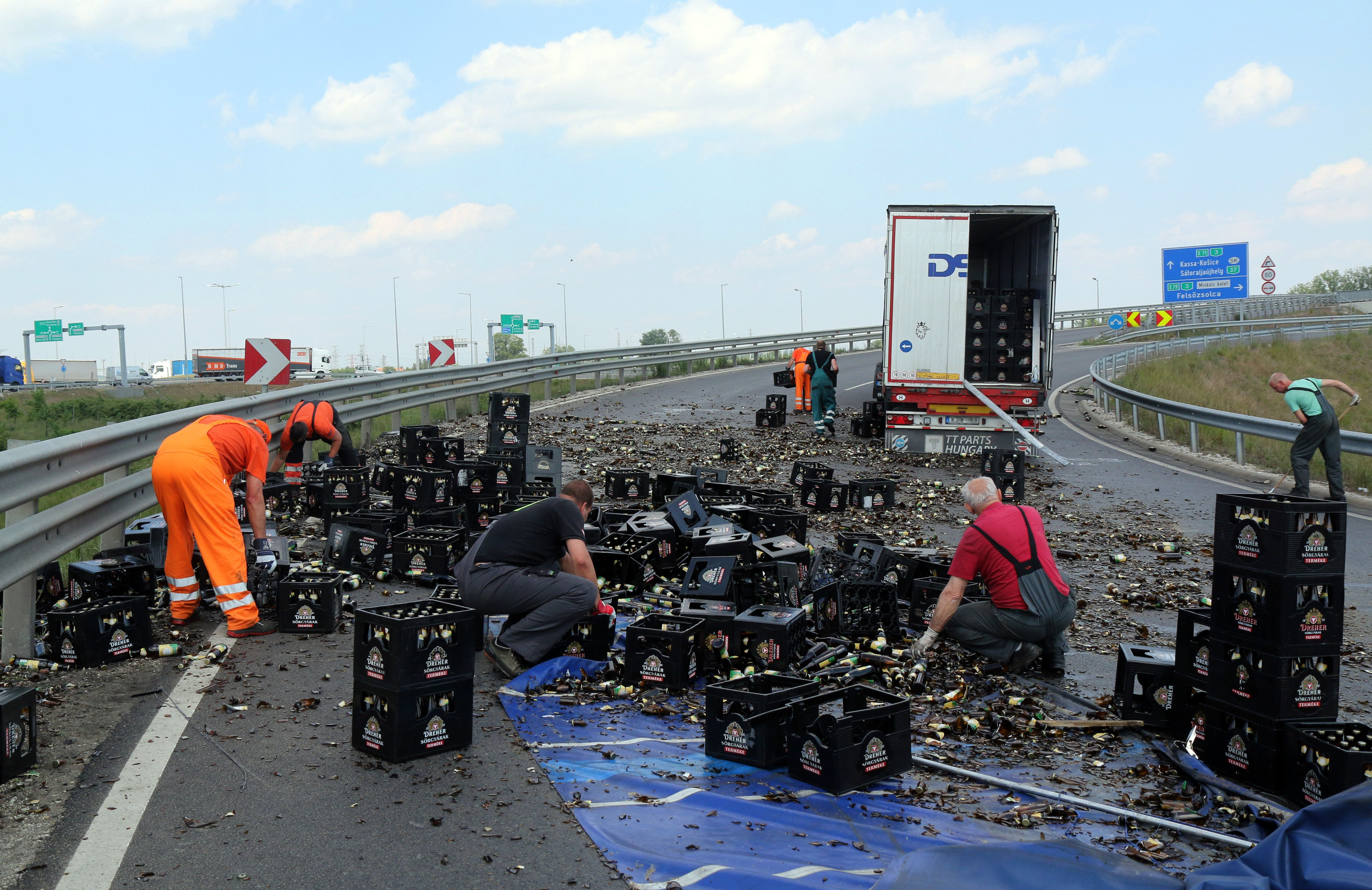 Egy teherautóról az úttestre esett és összetört sörösüvegeket takarítják el az M30-as autópálya lehajtóján Miskolc határában 2020. május 18-án. A kanyarban a teherautó rakományának egy része az úttestre borult. MTI/Vajda János