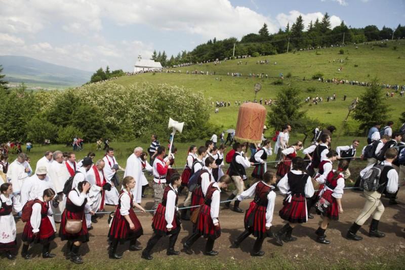 Csíksomlyó, 2014. június 7. A Kis- és Nagysomlyó-hegy közötti nyeregben felállított oltárhoz érkezõ zarándokok Csíksomlyón 2014. június 7-én. Középen a labarum, a csíksomlyói búcsú legfõbb jelvénye. MTI Fotó: Koszticsák Szilárd