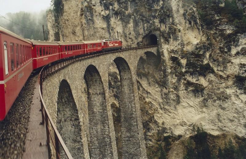 (GERMANY OUT) Der Bernina-Expreß der Schweizer Eisenbahn fährt über einen 65 Meter hohen Landwasser-Viadukt in einen Tunnel. Bahn, Brücke, Schweiz, Seilbahn, Viadukt, Zug Aufgenommen Mai 1996. (Photo by Klietz/ullstein bild via Getty Images)