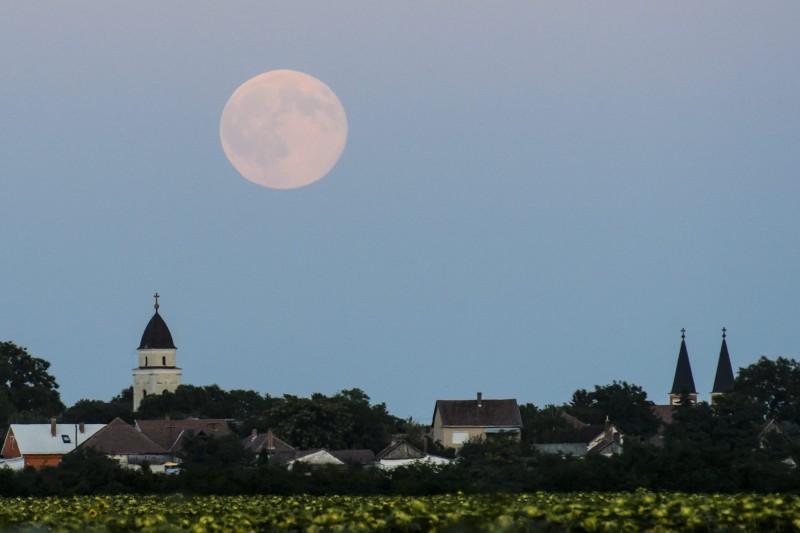 """Tiszaföldvár, 2015. augusztus 1. A felkelõ """"Kék Hold"""" Tiszaföldvárról fotózva 2015. július 31-én. Egy átlagos évben a Földrõl tizenkét teliholdat láthatunk, de ebben az évben tizenhármat. A jelenséget, amikor egy hónapban kétszer van telihold, """"Kék Holdnak"""" nevezzük. Júliusban 2-án és 31-én volt telihold. MTI Fotó: Komka Péter"""