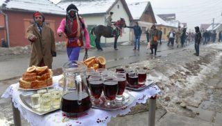 """Ürmös, 2017. február 5. Farsangi felvonulás résztvevõi Erdélyben, a Brassó megyei Ürmösön (Ormenis) 2017. február 4-én. A farsangon székely nõi és férfi népviseletbe öltözött fiatal férfiak vonulnak feldíszített lovakon, élükön kéregetõkkel az úgynevezett """"batyukásokkal"""" és rezesbandával a náddal borított kóborszekér, az úgynevezett """"bolond szekér"""" és a kísérõk elõtt. A társaság a falu összes utcáját végigjárja, de több kapunál is megállnak, ahol köményes pálinkát, fánkot és kürtõskalácsot kínálnak nekik. MTI Fotó: Kátai Edit"""