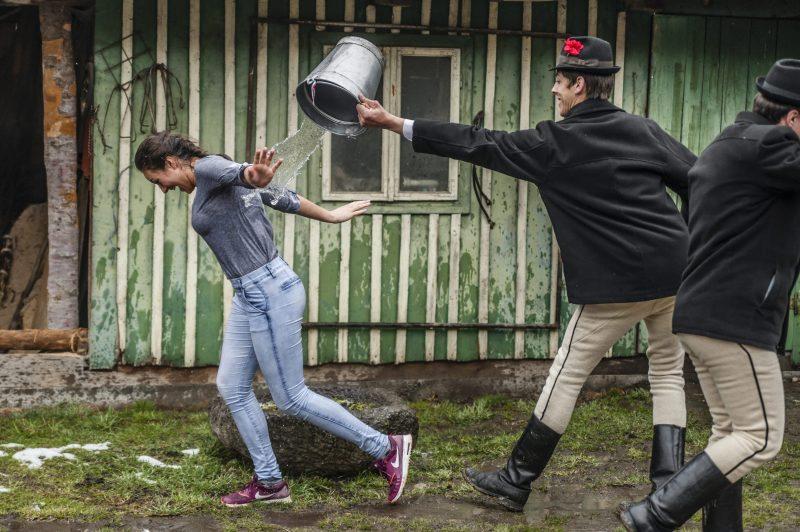 Csíkszentimre, 2016. március 28. Népviseletbe öltözött helyi fiatalok locsolnak meg egy vödör vízzel egy lányt az erdélyi Csíkszentkirályon 2016. március 28-án. MTI Fotó: Veres Nándor