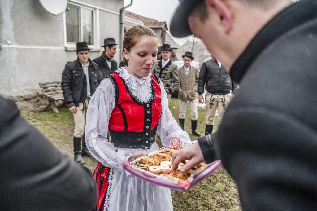 Csíkszentkirály, 2016. március 28. Süteménnyel kínálja az õt meglocsoló fiatalokat egy népviseletbe öltözött lány az erdélyi Csíkszentkirályon 2016. március 28-án. MTI Fotó: Veres Nándor
