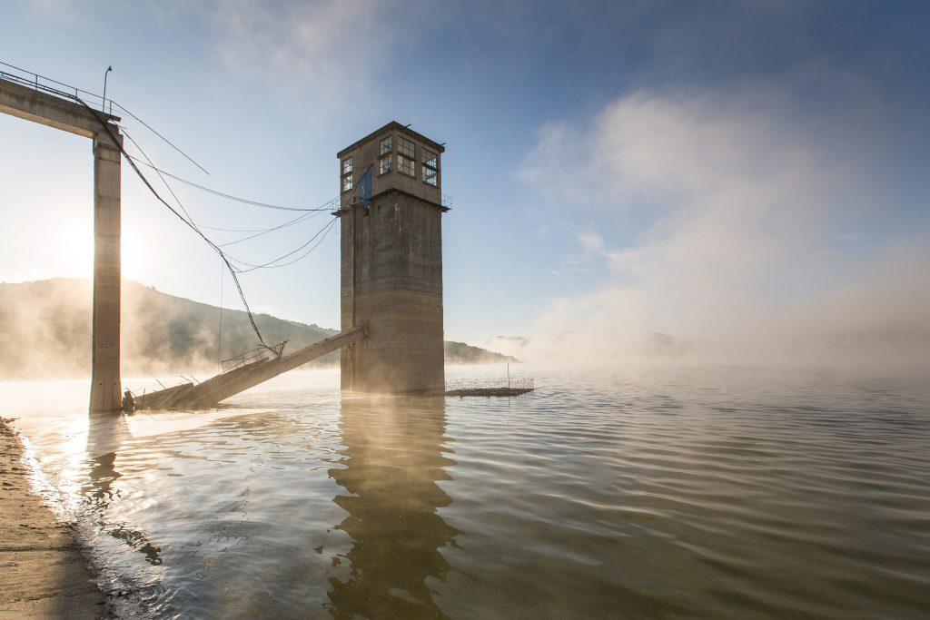 Bözödújfalu, 2017. május 21. A tóban álló irányítótornyot a gáttal összekötõ, sérült híd a Maros megyei Bözödújfalu mesterséges tavában 2017. május 21-én. Két hónap alatt több mint nyolc méterrel csökkentették a tó vízszintjét, így láthatóvá váltak az egykori település romjai. A következõ hetekben tovább apasztják a tározó vizét, hogy a vízgazdálkodási vállalat szakemberei meg tudják javítani a hidat, amelynek egyik összekötõ eleme februárban a vízbe esett. MTI Fotó: Boda L. Gergely