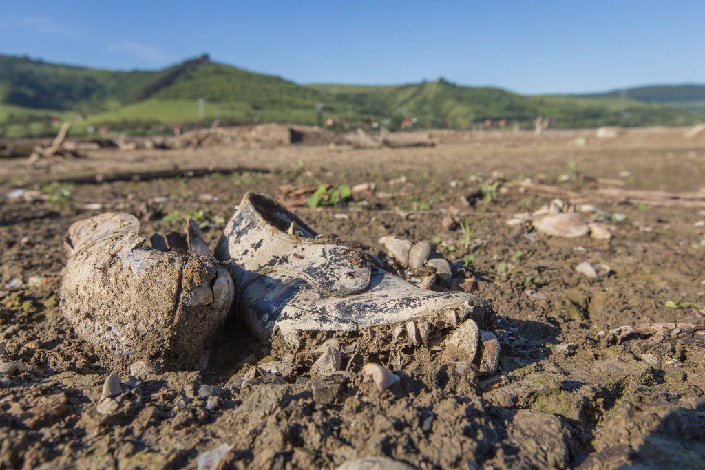 Bözödújfalu, 2017. május 21. Kagylókkal borított cipõ a leapasztott mesterséges tó medrében a Maros megyei Bözödújfalun 2017. május 21-én. Két hónap alatt több mint nyolc méterrel csökkentették a tó vízszintjét, így láthatóvá váltak az egykori település romjai. A következõ hetekben tovább apasztják a tározó vizét, hogy a vízgazdálkodási vállalat szakemberei meg tudják javítani a tóban álló irányítótornyot a gáttal összekötõ hidat, amelynek egyik összekötõ eleme februárban a vízbe esett. MTI Fotó: Boda L. Gergely