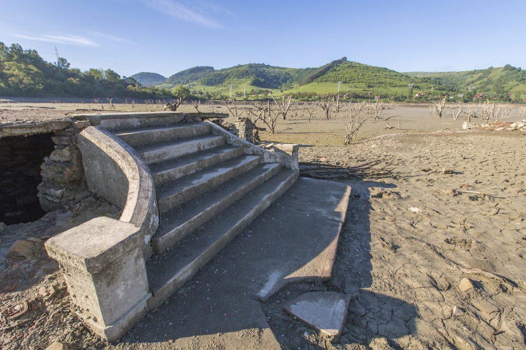 Bözödújfalu, 2017. május 21. A leapasztott mesterséges tó medre a Maros megyei Bözödújfalun 2017. május 21-én. Két hónap alatt több mint nyolc méterrel csökkentették a tó vízszintjét, így láthatóvá váltak az egykori település romjai. A következõ hetekben tovább apasztják a tározó vizét, hogy a vízgazdálkodási vállalat szakemberei meg tudják javítani a tóban álló irányítótornyot a gáttal összekötõ hidat, amelynek egyik összekötõ eleme februárban a vízbe esett. MTI Fotó: Boda L. Gergely