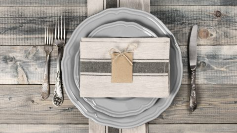 Table setting in rustic style on wooden table: gray plates, vintage silverware, linen napkins and blank rough tag. Top view point.