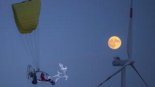 Sieversdorf, 2017. december 4. Mikulásnak öltözött férfi repül motoros sárkányrepülõvel és paplanernyõvel a németországi Sieversdorf közelében 2017. december 2-án. (MTI/AP/DPA/Patrick Pleul)