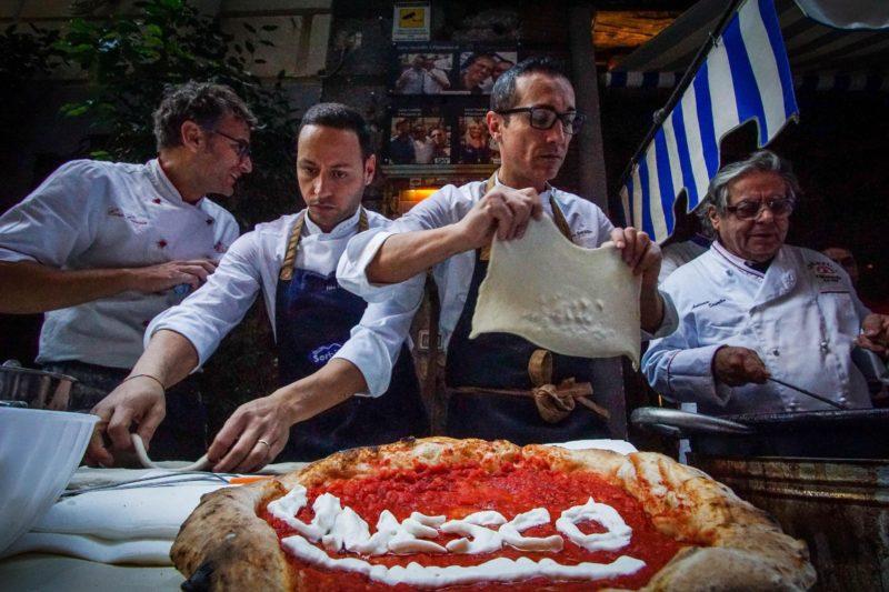 Nápoly, 2017. december 7. Az UNESCO nevével díszített pizzával ünnepelnek pizzakészítõk Nápolyban 2017. december 7-én, miután a nápolyi pizzakészítés mûvészete ezen a napon felkerült az ENSZ Nevelésügyi, Tudományos és Kulturális Szervezetének az emberiség szellemi kulturális örökségeit felvonultató listájára. A dél-olaszországi város felvételét megelõzõen mintegy kétmillióan írták alá a nápolyi pizzakészítés felterjesztését támogató petíciót. (MTI/EPA/Cesare Abbate)