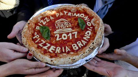 Nápoly, 2017. december 7. Az UNESCO nevével díszített pizzával ünnepelnek Nápolyvban 2017. december 7-én. A nápolyi pizzakészítés mûvészete ezen a napon felkerült az ENSZ Nevelésügyi, Tudományos és Kulturális Szervezetének az emberiség szellemi kulturális örökségeit felvonultató listájára. A dél-olaszországi város felvételét megelõzõen mintegy kétmillióan írták alá a nápolyi pizzakészítés felterjesztését támogató petíciót. (MTI/EPA/Ciro Fusco)