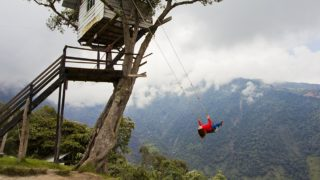 """Woman swinging at the famous swing at the """"End of the World"""" located at the La Casa del Árbol (The Treehouse) in Baños, Ecuador."""