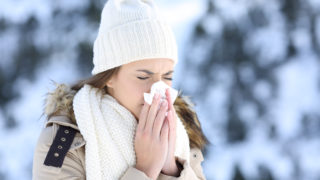 Woman blowing in a tissue in a cold winter with a snowy mountain in the background