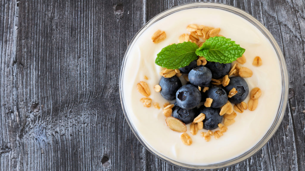 Bowl of yogurt with blueberries and granola, above view on rustic dark wood