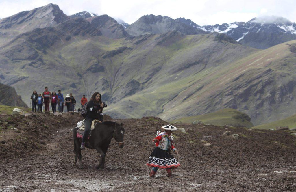 Cusco körzet, 2018. május 2. A 2018. március 2-i képen egy perui õslakos lóháton ülõ turistát vezet fel az Andok Vinicunca-hegyére, Cusco körzetben. Az 5200 méter tengerszint feletti magasságban tornyosuló Vinicunca, más néven Szivárvány-hegy oldalai a több millió éve lerakódott üledékrétegnek a földkéreg mozgása által láthatóvá vált színes sávjairól kapta a nevét, a turisták azonban csak a legutóbbi évtizedben fedezték fel a látványos természeti képzõdményt. (MTI/AP/Martin Mejia)