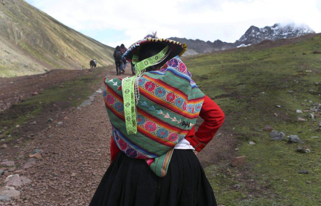 Cusco körzet, 2018. május 2. A 2018. március 2-i képen egy perui õslakos nõ turistákat vezet az Andok Vinicunca-hegyén, Cusco körzetben. Az 5200 méter tengerszint feletti magasságban tornyosuló Vinicunca, más néven Szivárvány-hegy oldalai a több millió éve lerakódott üledékrétegnek a földkéreg mozgása által láthatóvá vált színes sávjairól kapta a nevét, a turisták azonban csak a legutóbbi évtizedben fedezték fel a látványos természeti képzõdményt. (MTI/AP/Martin Mejia)