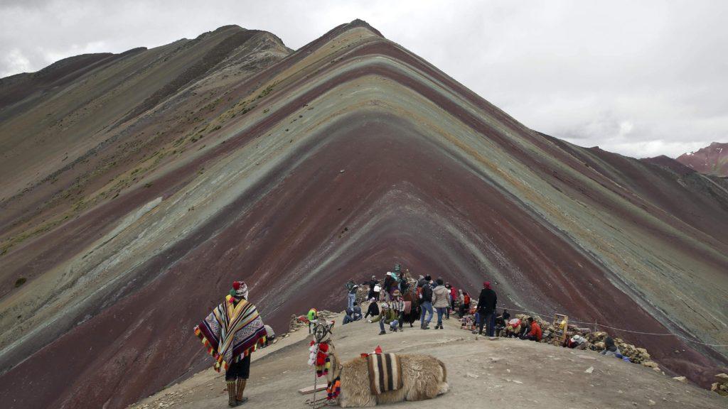 Cusco körzet, 2018. május 2. A 2018. március 2-i képen perui õslakosok turistákat vezetnek fel az Andok háttérben levõ Vinicunca-hegyére, Cusco körzetben. Az 5200 méter tengerszint feletti magasságban tornyosuló Vinicunca, más néven Szivárvány-hegy oldalai a több millió éve lerakódott üledékrétegnek a földkéreg mozgása által láthatóvá vált színes sávjairól kapta a nevét, a turisták azonban csak a legutóbbi évtizedben fedezték fel a látványos természeti képzõdményt. (MTI/AP/Martin Mejia)