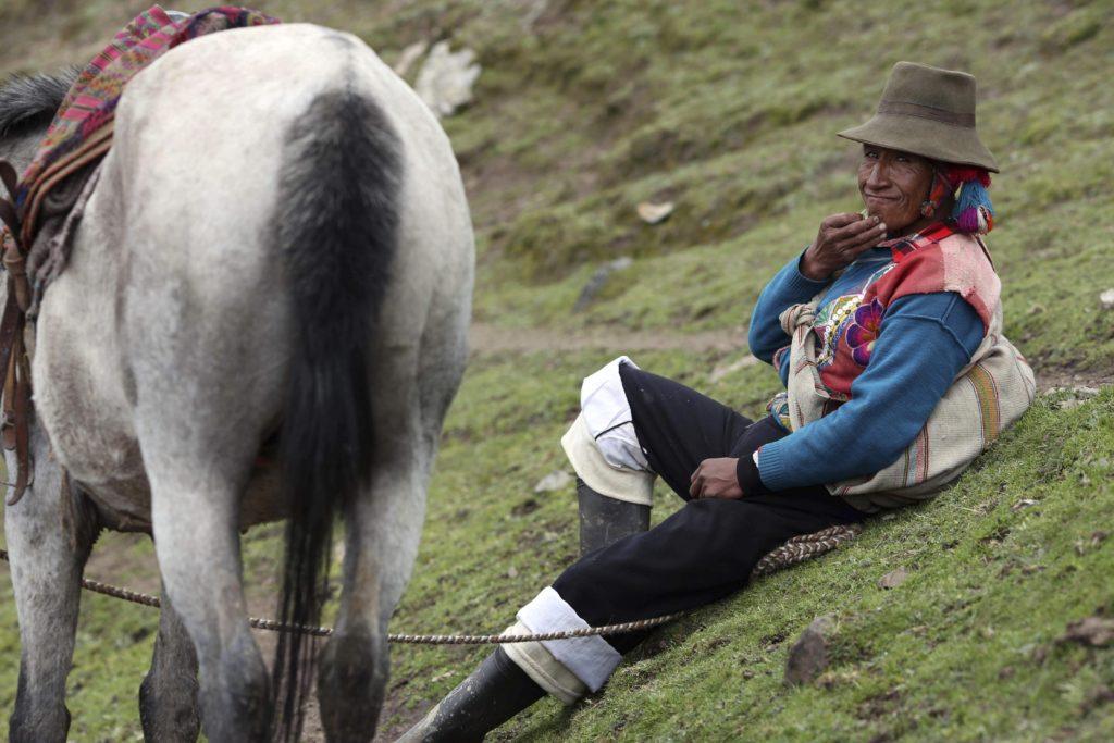 Cusco körzet, 2018. május 2. A 2018. március 2-i képen egy perui õslakos túravezetõ megpihen az Andok Vinicunca-hegyén, Cusco körzetben. Az 5200 méter tengerszint feletti magasságban tornyosuló Vinicunca, más néven Szivárvány-hegy oldalai a több millió éve lerakódott üledékrétegnek a földkéreg mozgása által láthatóvá vált színes sávjairól kapta a nevét, a turisták azonban csak a legutóbbi évtizedben fedezték fel a látványos természeti képzõdményt. (MTI/AP/Martin Mejia)