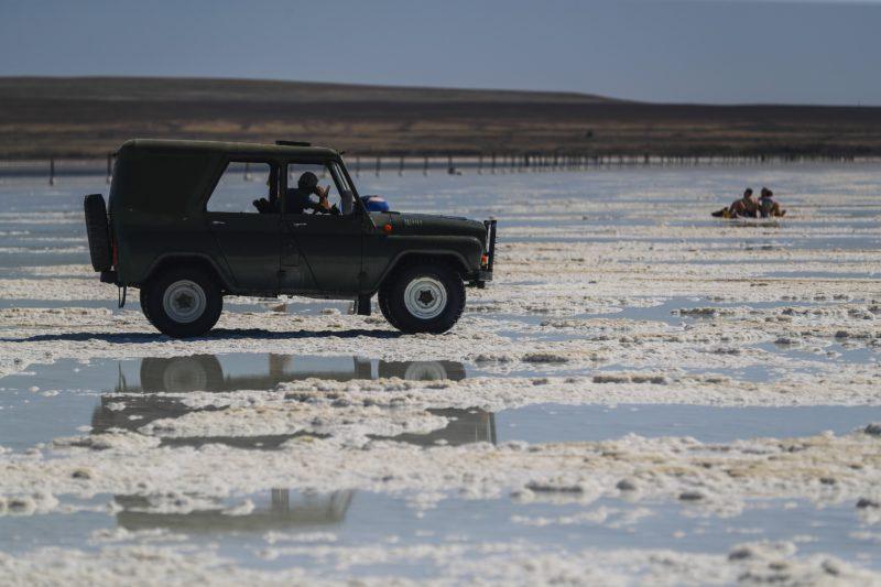 Nyizsnij Baszkuncsak, 2018. június 25. Fuvarra vár terepjárójában egy helybeli férfi a sekély vizû Baszkuncsak-tónál a délnyugat-oroszországi Asztrahán régióban fekvõ Nyizsnij Baszkuncsak falu közelében 2018. június 23-án. A kazah határhoz közeli sóstó 21 méterrel a tengerszint alatt terül el 53 négyzetkilométeren. A tóvíz éves átlagban 300 gramm literenkénti sótartalma megközelíti a Holt-tengerét, és ahhoz hasonlóan a baktériumokon kívül semmilyen más élõlény nem képes megélni benne. A Baszkuncsak-tó a Kaszpi-mélyföldön fekszik, amely a földtörténeti negyedidõszakban tengerfenék volt, és sós vizét egy 11 ezer négyzetkilométer gyûjtõterületû folyó táplálja. A sókiválásokat a 8. századtól bányásszák, jelenleg évente 1,5-5 millió tonna mennyiségben, az Oroszországban kitermelt étkezési só 80 százaléka innen származik. A helybeliek keresetük kiegészítéseként turistákat szállítanak a tópartra régi katonai dzsipekben, mert a sóstó az 1997-ben szigorúan védetté nyilvánított Bogyinszko-Baszkunszcsakszki Természetvédelmi Területen fekszik, ahova a látogatók saját autóval nem hajthatnak be. (MTI/EPA/Szergej Ilnyickij)