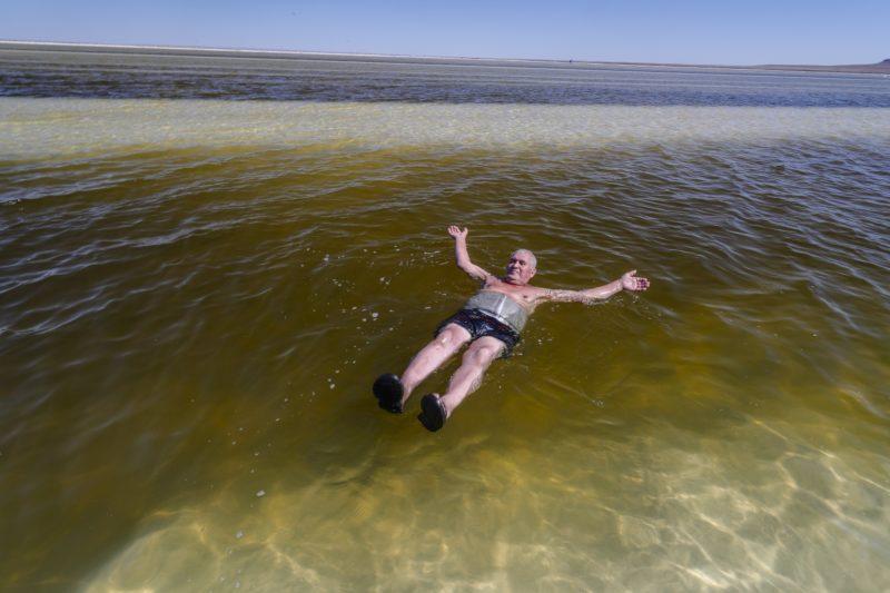 Nyizsnij Baszkuncsak, 2018. június 25. A sekély vizû Baszkuncsak-tóban mártózik meg egy férfi a délnyugat-oroszországi Asztrahán régióban fekvõ Nyizsnij Baszkuncsak falu közelében 2018. június 23-án. A kazah határhoz közeli sóstó 21 méterrel a tengerszint alatt terül el 53 négyzetkilométeren. A tóvíz éves átlagban 300 gramm literenkénti sótartalma megközelíti a Holt-tengerét, és ahhoz hasonlóan a baktériumokon kívül semmilyen más élõlény nem képes megélni benne. A Baszkuncsak-tó a Kaszpi-mélyföldön fekszik, amely a földtörténeti negyedidõszakban tengerfenék volt, és sós vizét egy 11 ezer négyzetkilométer gyûjtõterületû folyó táplálja. A sókiválásokat a 8. századtól bányásszák, jelenleg évente 1,5-5 millió tonna mennyiségben, az Oroszországban kitermelt étkezési só 80 százaléka innen származik. A helybeliek keresetük kiegészítéseként turistákat szállítanak a tópartra régi katonai dzsipekben, mert a sóstó az 1997-ben szigorúan védetté nyilvánított Bogyinszko-Baszkunszcsakszki Természetvédelmi Területen fekszik, ahova a látogatók saját autóval nem hajthatnak be. (MTI/EPA/Szergej Ilnyickij)