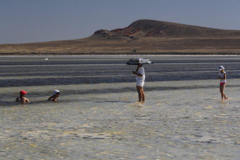Nyizsnij Baszkuncsak, 2018. június 25. Fürdõzõk a sekély vizû Baszkuncsak-tóban, a délnyugat-oroszországi Asztrahán régióban fekvõ Nyizsnij Baszkuncsak falu közelében 2018. június 23-án. A kazah határhoz közeli sóstó 21 méterrel a tengerszint alatt terül el 53 négyzetkilométeren. A tóvíz éves átlagban 300 gramm literenkénti sótartalma megközelíti a Holt-tengerét, és ahhoz hasonlóan a baktériumokon kívül semmilyen más élõlény nem képes megélni benne. A Baszkuncsak-tó a Kaszpi-mélyföldön fekszik, amely a földtörténeti negyedidõszakban tengerfenék volt, és sós vizét egy 11 ezer négyzetkilométer gyûjtõterületû folyó táplálja. A sókiválásokat a 8. századtól bányásszák, jelenleg évente 1,5-5 millió tonna mennyiségben, az Oroszországban kitermelt étkezési só 80 százaléka innen származik. A helybeliek keresetük kiegészítéseként turistákat szállítanak a tópartra régi katonai dzsipekben, mert a sóstó az 1997-ben szigorúan védetté nyilvánított Bogyinszko-Baszkunszcsakszki Természetvédelmi Területen fekszik, ahova a látogatók saját autóval nem hajthatnak be. (MTI/EPA/Szergej Ilnyickij)