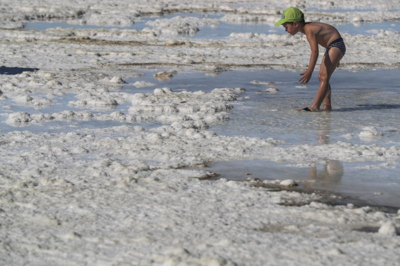 Nyizsnij Baszkuncsak, 2018. június 25. Kisfiú a sekély vizû Baszkuncsak-tónál, a délnyugat-oroszországi Asztrahán régióban fekvõ Nyizsnij Baszkuncsak falu közelében 2018. június 23-án. A kazah határhoz közeli sóstó 21 méterrel a tengerszint alatt terül el 53 négyzetkilométeren. A tóvíz éves átlagban 300 gramm literenkénti sótartalma megközelíti a Holt-tengerét, és ahhoz hasonlóan a baktériumokon kívül semmilyen más élõlény nem képes megélni benne. A Baszkuncsak-tó a Kaszpi-mélyföldön fekszik, amely a földtörténeti negyedidõszakban tengerfenék volt, és sós vizét egy 11 ezer négyzetkilométer gyûjtõterületû folyó táplálja. A sókiválásokat a 8. századtól bányásszák, jelenleg évente 1,5-5 millió tonna mennyiségben, az Oroszországban kitermelt étkezési só 80 százaléka innen származik. A helybeliek keresetük kiegészítéseként turistákat szállítanak a tópartra régi katonai dzsipekben, mert a sóstó az 1997-ben szigorúan védetté nyilvánított Bogyinszko-Baszkunszcsakszki Természetvédelmi Területen fekszik, ahova a látogatók saját autóval nem hajthatnak be. (MTI/EPA/Szergej Ilnyickij)