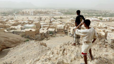 Sibám, 2018. július 20. A 2018. július 12-i képen jemeni férfiak nézik egy magaslatról a közép-jemeni Hadramaut kormányzóság Sibám városát. A Ramlat asz-Szabátajn-sivatagban a 3. században alapított Sibám vályogtéglából rakott, többemeletes lakóházairól híres. A jelenlegi házállomány javarészt a 16. századból származik, számos lakóépületet többször is újjáépítettek az utóbbi évszázadokban. A vertikális építkezés elvén alapuló várostervezés egyik legrégebbi példájaként szolgáló Sibámot gyakran nevezik a világ legrégebbi felhõkarcoló-városának, avagy a sivatag Manhattanjének. (MTI/EPA/Jajha Arhab)
