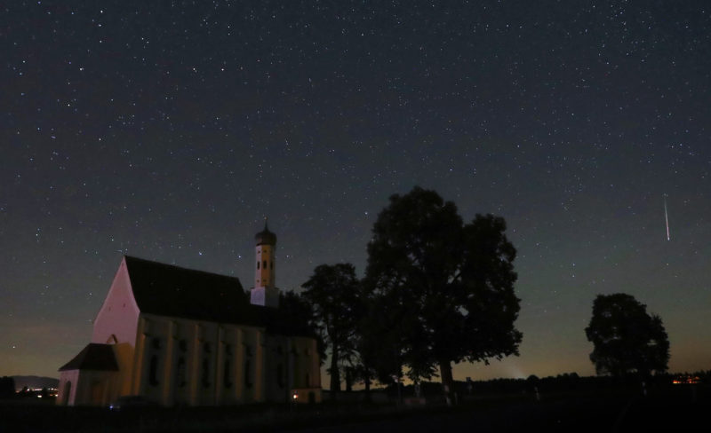 A meteor crosses the night sky on early August 12, 2018 behind the Sankt Coloman pilgrimage church in Fuessen, southwestern Germany, during the annual Perseid meteor shower. / AFP PHOTO / dpa / Karl-Josef Hildenbrand / Germany OUT
