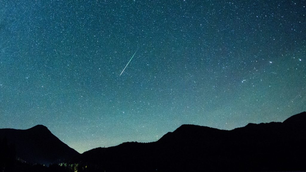 12 August 2018, Germany, Einsiedl: A shooting star appears next to the Milky Way in the sky above Walchensee. Every year in August numerous shooting stars can be seen in the shooting star showers of the Perseids. Photo: Matthias Balk/dpa