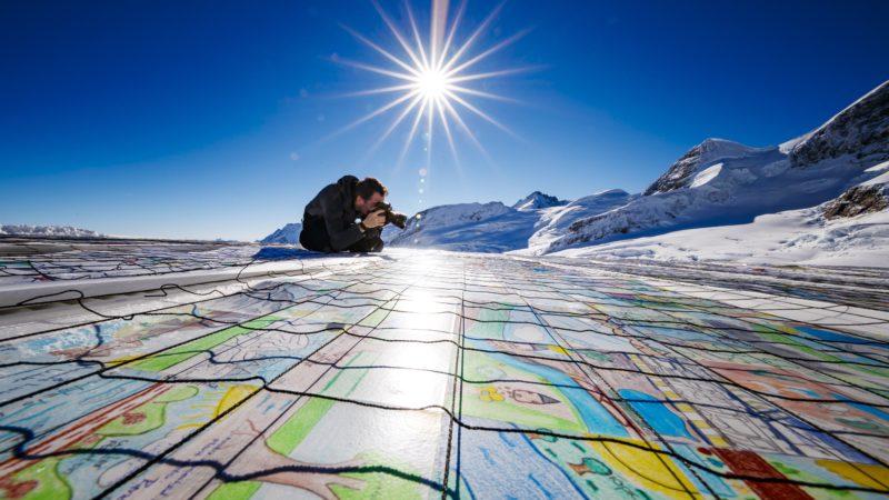 Jungfrau-nyereg, 2018. november 16. Óriási, mintegy 2500 négyzetméteres, több mint 125 ezer normál méretû postai képeslapból összeállított képeslap az Aletsch-gleccseren, a Jungfrau 3466 méteres magasságban húzódó nyergének közelében 2018. november 16-án. Az eredeti képeslapokat a villág 35 országából írták gyermekek és fiatalok a klímaváltozás és a globális felmelegedés ellen szót emelve. A szervezõk a képeslapóriással szeretnének bekerülni a Guinness Rekordok Könyvébe. MTI/EPA/KEYSTONE/Valentin Flauraud