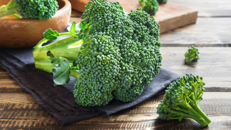Healthy green organic raw broccoli on wooden table
