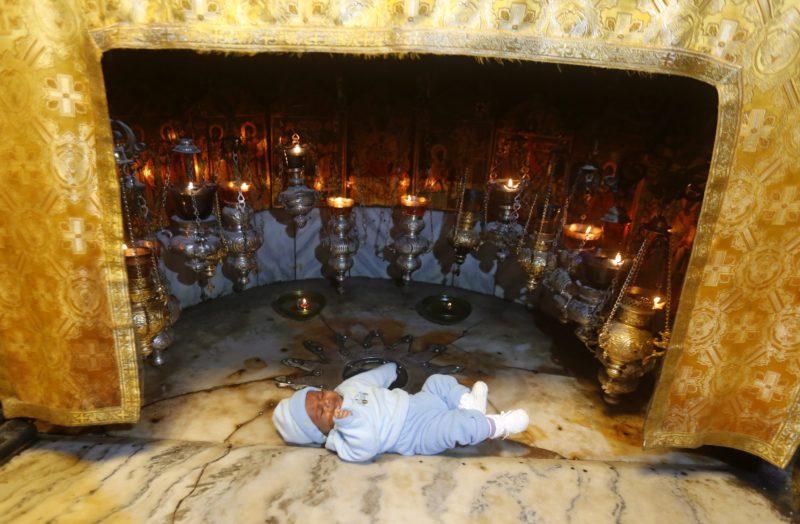 Betlehem, 2015. december 22. Egy csecsemõt fektettek hívõk a Jézus Krisztus szülõhelyét jelzõ tizennégy ágú ezüstcsillagra a betlehemi Születés templomának altemplomában 2015. december 22-én. Az altemplom pontosan azon a helyen, abban a barlangban épült, ahol a keresztények hite szerint Jézus megszületett. (MTI/EPA/Abed al-Haslamun)