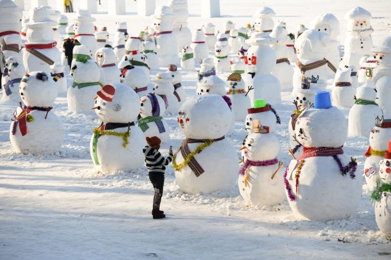 (190103) -- BEIJING, Jan. 3, 2019 (Xinhua) -- A woman takes photos of snowman sculptures on the riverbank of Songhua River in Harbin, capital of northeast China's Heilongjiang Province, Jan. 2, 2019. (Xinhua/Wang Song) XINHUA PHOTOS OF THE DAY