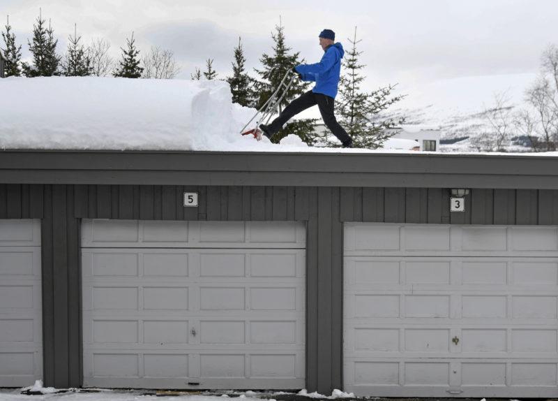 Tromsö, 2019. április 1. Magne Henriksen havat takarít le garázsának tetejérõl a norvégiai Tromsöben 2019. április 1-jén. A nagy havazás eredményeképpen a hó vastagsága a 158 centimétert is eléri az ország északi részén. MTI/EPA/NTB SCANPIX/Rune Stoltz Bertinussen