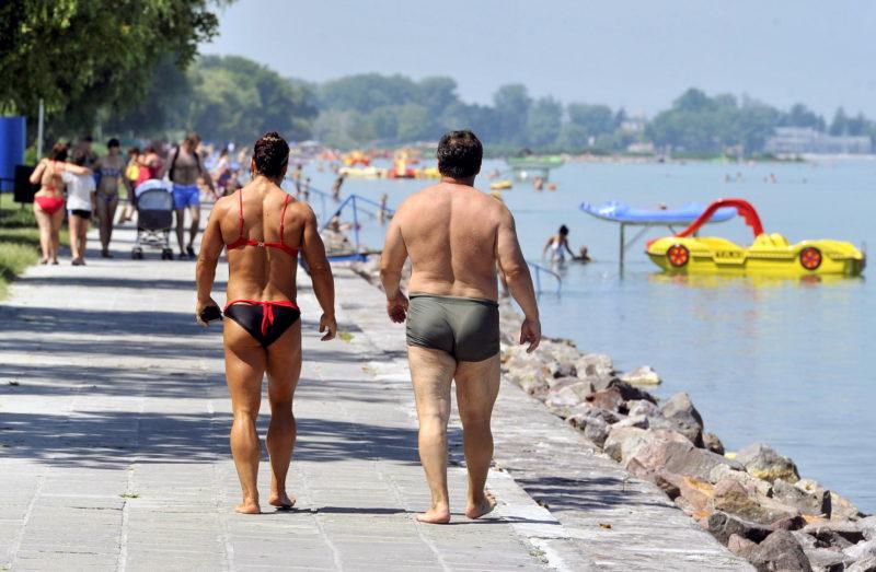 Siófok, 2013. június 19. Fürdõruhát viselõ nõ és férfi sétál a Balaton partján, a siófoki Aranyparton 2013. június 19-én. Június 19-re virradóra több helyen is megdõlt az eddigi legmagasabb napi minimumhõmérsékleti rekord. A legmagasabb értéket hajnalban a Kab-hegyen mérték, ahol csak 24,2 Celsius-fokra csökkent a hõmérséklet. Az elõrejelzés szerint a legmagasabb nappali hõmérséklet 31 és 36 fok között alakul. MTI Fotó: Máthé Zoltán