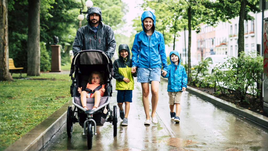 A Family with childs walk on rainy day with raincoat